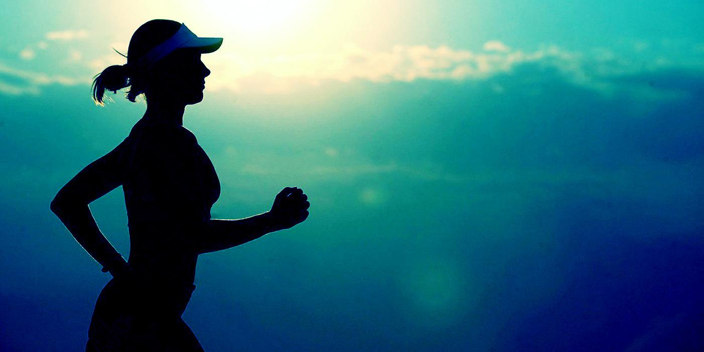 Runner silhouetted against sunset